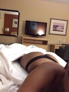 Cara in a hotel room, just under the covers with her thong and bottom showing in post titled Cloudy Day