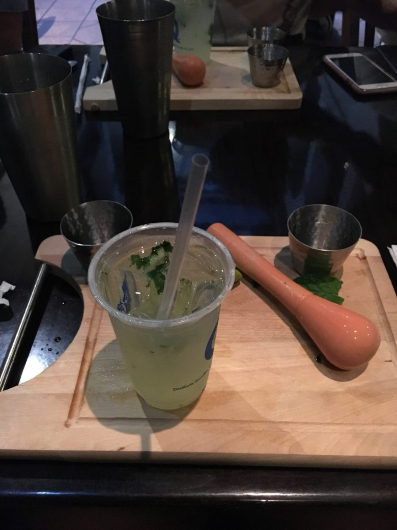 A green alcoholic drink, freshly made on a chopping board with pestle beside in it, in post titled #SoSS
