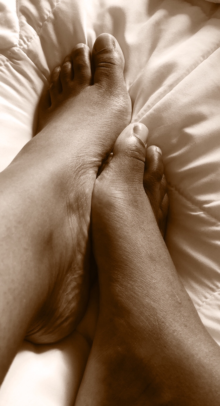 Cara's feet on a bed in gray scale/sepia