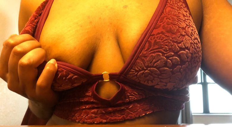 Cara in a velvet bra holding her breast