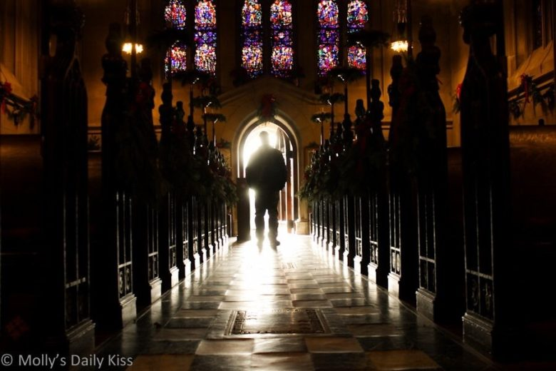A church aisle with a man in silhouette standing in the sunshine