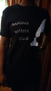Cara in a black shirt that says Anxious Writers Club in White lettering
