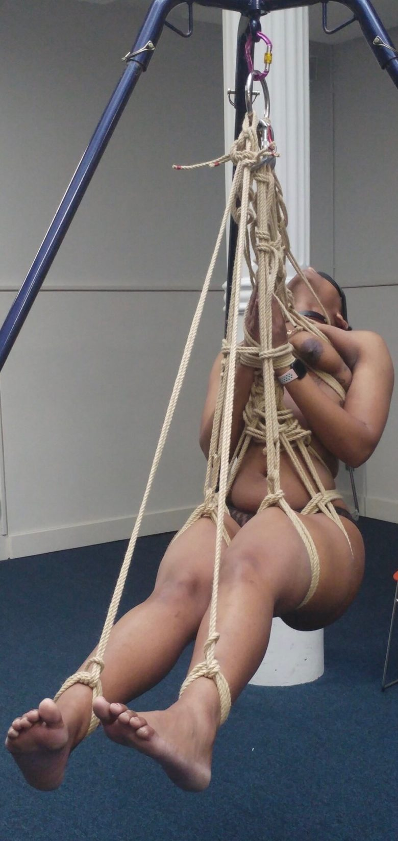 Cara bound and suspended with rope from a suspension frame